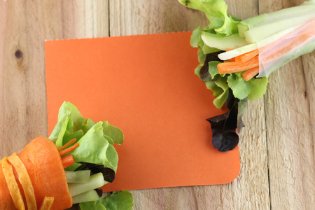 note paper: rolls of salad and note paper on wood background.