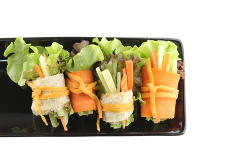 black dish: rolls of salad in the black dish on white background Stock Photo
