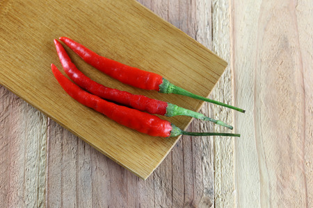 red peppers: Red peppers in bamboo dish on wood background.