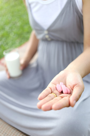 vitamin pill: Pregnant women have a glass of Milk and vitamin pill in hand to eat for health of the baby.