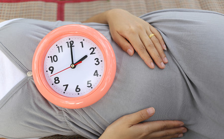 show time: Pregnant women show clock on her belly to tell the time two oclock.