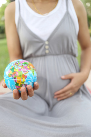 create idea: Pregnant women show Globe model in hand are the idea of Mother is people create a World.