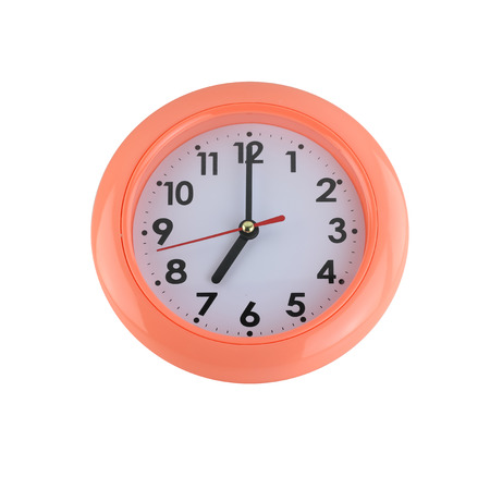 seven o'clock: orange wall clock isolated on white background. Stock Photo