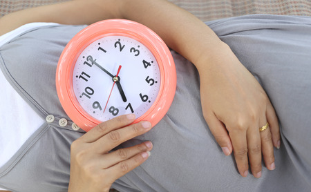 show time: Pregnant women show clock on her belly to tell the time seven oclock.