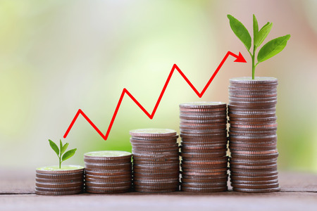 silver coin stack and arrow line in business growth concept on wood floor with colorful nature background.