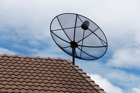 satellite dish: satellite dish on the house roof in bright day. Stock Photo