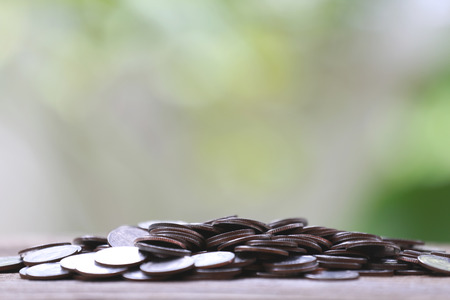 wood floor: pile silver coin on a wood floor and colorful bokeh background.