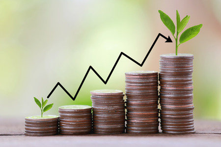 trading floor: silver coin stack and arrow line in business growth concept on wood floor with colorful nature background.