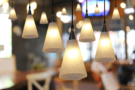 lighting: Warm lighting modern ceiling lamps in the cafe and interior decoration restaurant. Stock Photo