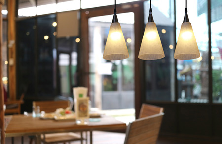 hanging on: Warm lighting modern ceiling lamps in the cafe and interior decoration restaurant. Stock Photo