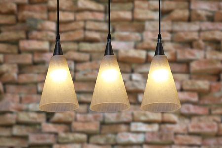 ceiling lamps: Warm lighting modern ceiling lamps on old brick wall background. Stock Photo