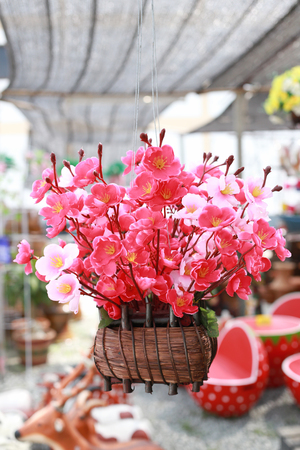 hung: Artificial pink cherry blossoms in the flower pot hung for decoration. Stock Photo