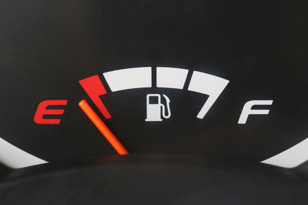 Fuel gauge with warning indicating low fuel tank,Gas gauge indicating white icon for gas station. Stock Photo
