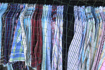 blocking: clothes fashion is hanging clothesline in shop wear and a nets blocking to sell. Stock Photo