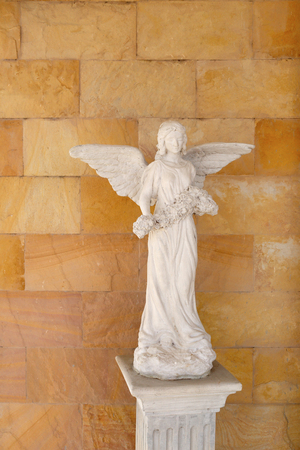 angel statue: Old Angel statue with have a backdrop is brown brick wall. Stock Photo