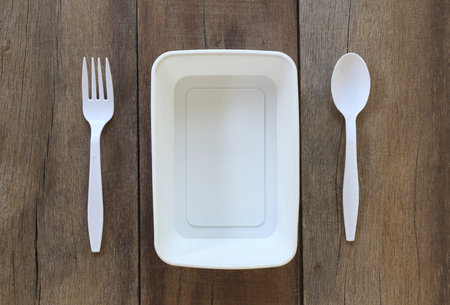 housewares: White plastic bowl and have spoon,fork on old wood background.
