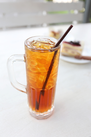 quencher: Iced tea and white tube in glass on the coffee shop table. Stock Photo