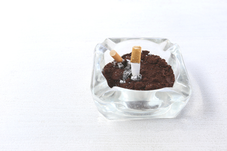 cancers: Ashtray on the white table for disposable cigarette after smoking it. Stock Photo