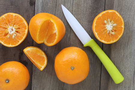 mandarin oranges: Mandarin oranges and acrylic knife placed on the old wooden floor,design concept for about health foods. Stock Photo