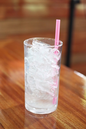 suction: Ice in the glass is placed on the the dining table and have pink suction tube. Stock Photo