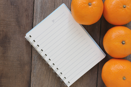 mandarin oranges: Notebook and Mandarin oranges placed on the old wooden floor,design concept for about health foods.