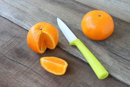placed: fresh orange fruit placed on wooden floor and have knife acrylic for concept of healthy eating.