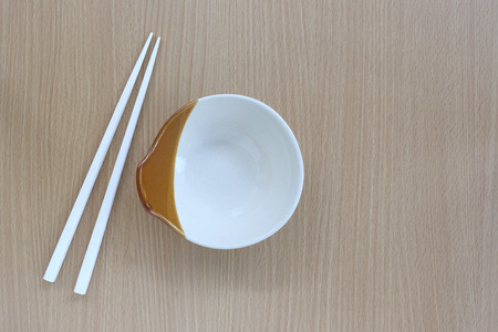 housewares: white chopsticks and cup in top view on wood background for design concept food.