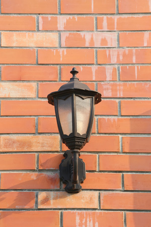 mounted: Black Lantern mounted on brown brick wall in exterior. Stock Photo