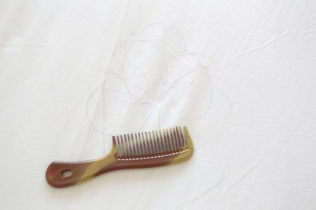 tela blanca: Peine y el pelo negro de la mujer puesta en tela blanca en el concepto del problema de p�rdida de cabello. Foto de archivo