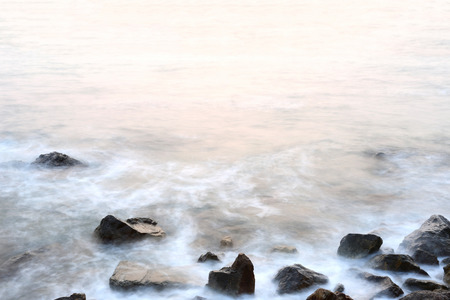 softness: Sea mist softness of the tides and sunset at evening with rocks in foreground,viewpoint in Chanthaburi Thailand.