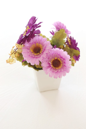 housewares: Vintage pink and violet artificial flowers on a white fabric in the bedroom interior concept and design. Stock Photo