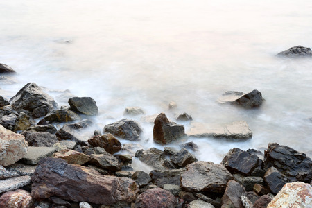 tides: Sea mist softness of the tides and sunset at evening with rocks in foreground,viewpoint in Chanthaburi Thailand.