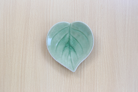 leaf shape: Green leaf shape dish in top view on wood background for design concept food. Stock Photo