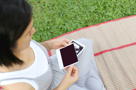 show garden: Asian Pregnant women show ultrasound film baby picture on her belly in hand at garden.