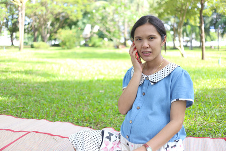 care about the health: Asian pregnant women using smartphones call to doctor and query about in health care in the public park.