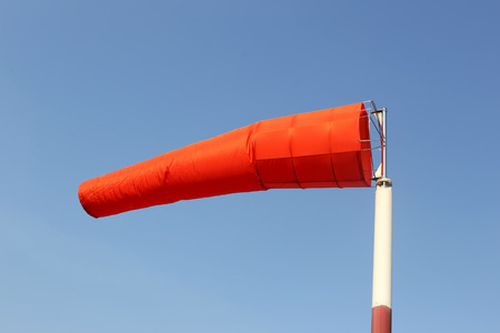 day time: Wind sock of equipment check the wind blow direction in day time on blue sky background.