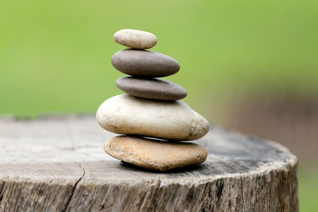 Balance Stones stacked to pyramid in the soft green background to Spa ideas design or freedom and stability concept on rocks. Banque d'images