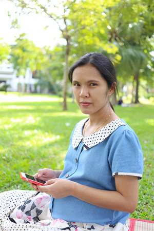 care about the health: Pregnant women using smartphones to search for information about health care in the public park.