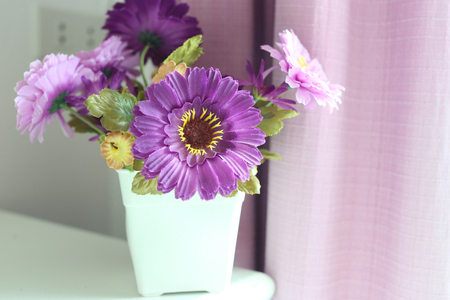 adorning: Purple flowers artificial in a white vase placed beside the window in the bedroom.