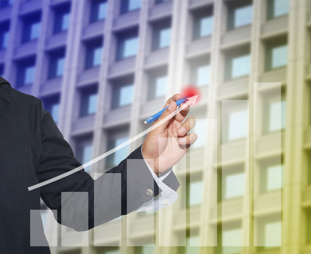 perfect fit: Hand of businessman drawing graphics a perfect fit point growing graph to concept of profit in business and have skyscraper background.