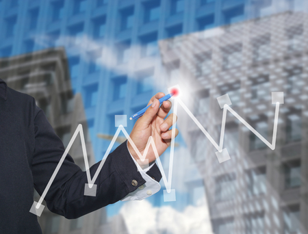 business graphics: Hand of businessman drawing graphics a top point growing graph to concept of profit in business and have skyscraper background.