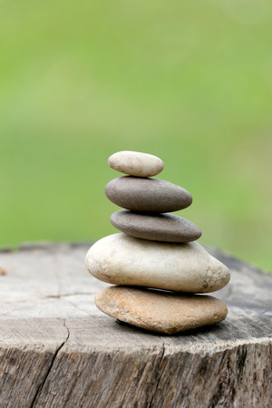 Balance Stones stacked to pyramid in the soft green background to Spa ideas design or freedom and stability concept on rocks. Stock Photo