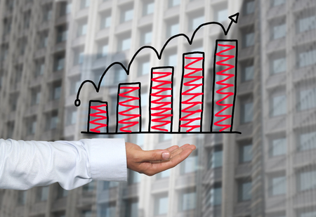 point of demand: Drawing graphics growing graph on hand to concept of investment profit in business and have skyscraper background. Stock Photo