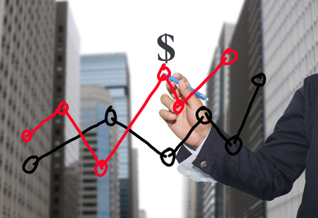 point of demand: Hand of businessman drawing graphics a top point growing graph to concept of investment profit in business and have skyscraper background.