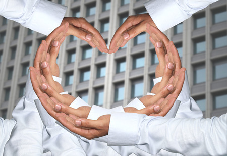 concatenation: Hand of men concatenation a heart shape and have Skyscraper of background. Stock Photo