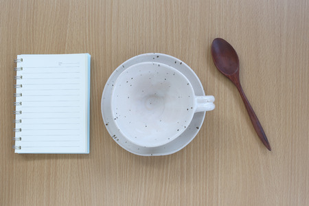 housewares: White coffee cup and note book in top view on wood background for design concept food. Stock Photo