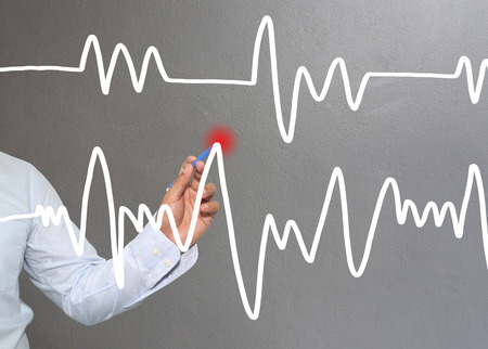 point of demand: Hand of businessman drawing graphics a top point growing graph to concept of investment profit in business and have Gray wall of background. Stock Photo