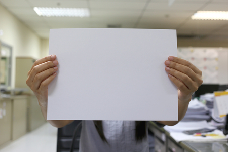 input: Womans hand holding a blank white paper for input text to Design Concepts background.