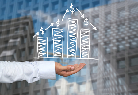 Drawing graphics growing graph on hand to concept of investment profit in business and have skyscraper background. Stock Photo