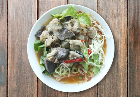 Curry chicken noodles (KHANOM CHIN) with vegetable,This is local Thai foods in Vermicelli rice on wooden background.